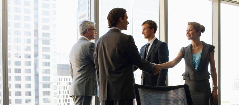 Image of group shaking hands in a conference room